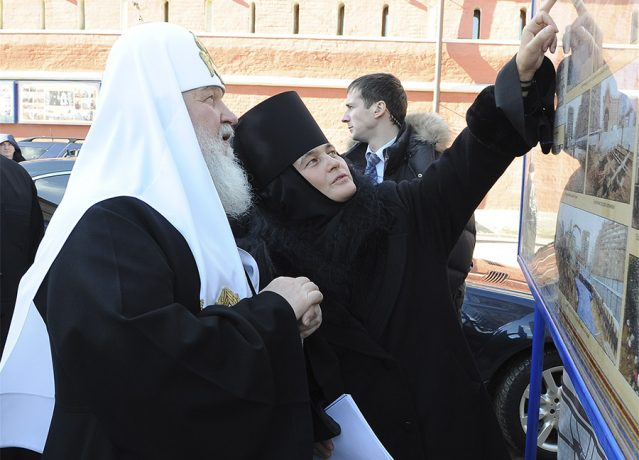 Abbess Feofaniya shows to the Primate of the Russian Church photographs of the work performed stages